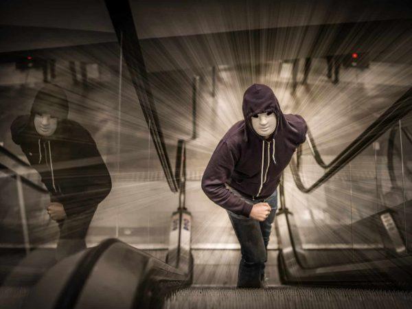 Mann kommt bedrohlich mit einer weißen Maske die Rolltreppe hoch